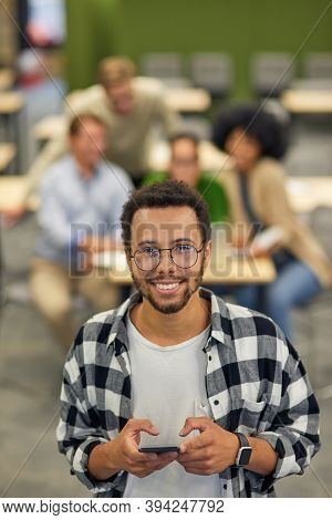 Young Happy Mixed Race Man Holding Smartphone And Smiling At Camera While Standing In Coworking Spac