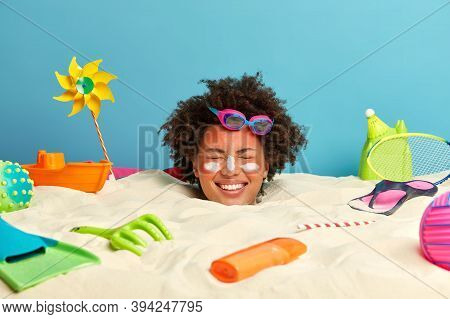 Smiling Optimistic Woman With Afro Hairstyle Closes Eyes And Smiles Broadly, Wears Swimming Goggles,