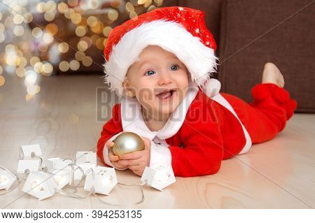 Christmas Child. Happy Adorable Baby Dressed As Santa Plays With Christmas Balls Over Holidays Light