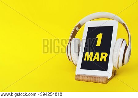 March 1st . Day 1 Of Month, Calendar Date. Stylish Headphones And Modern Tablet On Yellow Background
