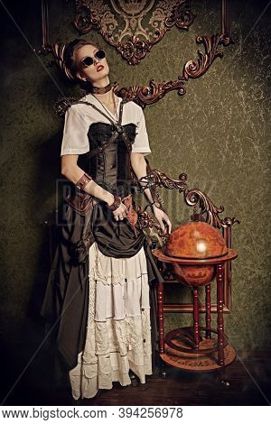 Full length portrait of a beautiful steampunk lady standing in a room with Victorian vintage interior. Steampunk world.