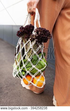 Girl Is Holding Mesh Shopping Bag With Vegetables, Greens Without Plastic Bags. Zero Waste, Plastic