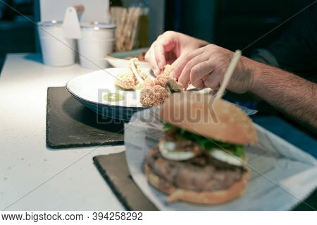 Chef Cooks Vegan Food, Vegan Hamburger And Fried Mushrooms. Vegan Food Concept. Focus On Fried Mushr