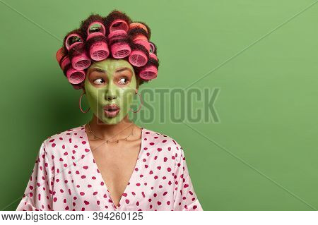 Studio Shot Of Impressed Shocked Woman Applies Fresh Clay Mask For Healthy Skin, Does Beauty Procedu