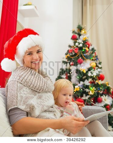 Smiling Mother And Baby Girl Using Tablet Pc Near Christmas Tree