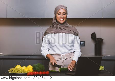 Cheerful Arab Woman Cooking At Laptop Learning To Cook Food Watching Videos Of Healthy Recipes Onlin