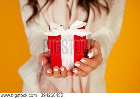 Happy Young Smiling Woman Holding And Holding Red Gift Box In Front, Offering And Giving Christmas G