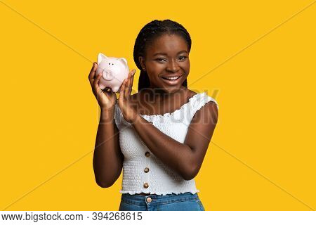 Money Savings. Cheerful Black Woman Posing With Piggy Bank Over Yellow Studio Background, Smart Afri