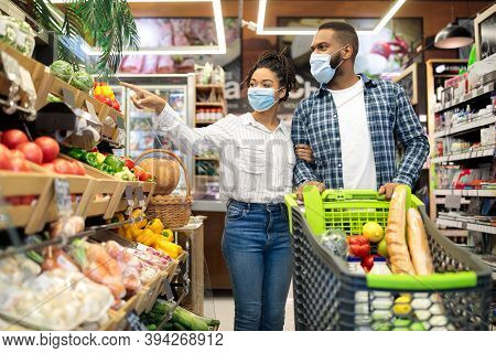 Supermarket Buyers. African American Couple Doing Grocery Shopping Together, Buying Healthy Food Pro