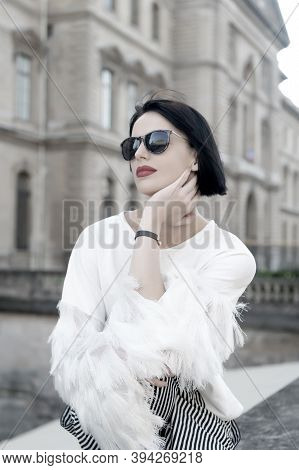 Girl In Sunglasses Pose On House Facade In Paris, France. Woman With Red Lips And Brunette Hair. Mod