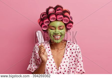 Happy Positive Young Woman Stands With Closed Eyes, Holds Delicious Ice Cream, Applies Hair Rollers,