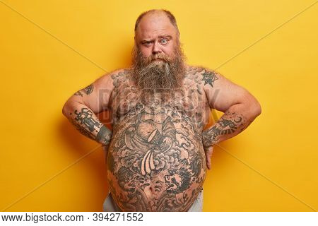 Serious Bearded Fat Man Has Thick Beard, Tattooed Body And Big Belly, Looks From Under Eyebrows, Kee