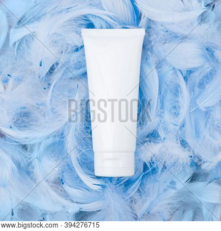 Spa Cosmetic Product, White Cream Tube, Branding Mock Up, Top View On Blue Feathers Background. Flat
