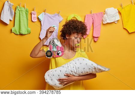 Photo Of Lovely Mommy Looks At Baby And Tries To Sooth Naughtly Newborn, Shows Mobile And Sucks Nipp
