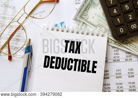 Notebook With The Text Tax Deductible On The Office Table Among The Stationery.