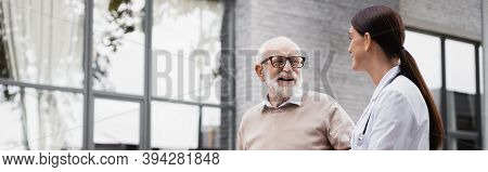 Elderly Man And Social Worker Looking At Each Other While Strolling Outside, Banner
