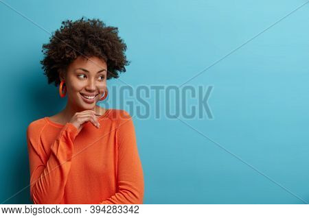 Studio Shot Of Ethnic Curly Woman Touches Chin Gently, Feels Happy And Delighted, Turns Face Aside,