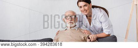 Nurse Hugging Shoulders Of Elderly Man While Looking At Camera, Banner