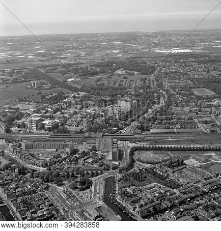 Leiden, Holland, June 03 - 1983: Historical black and white aerial photo of the Station quarter in Leiden and railway station