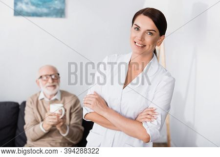 Social Worker Smiling At Camera While Standing With Crossed Arms Near Aged Man Holding Cup Of Tea