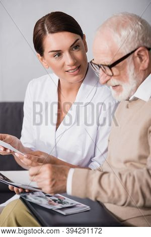 Social Worker Looking At Aged Mad While Holding Book On Blurred Foreground