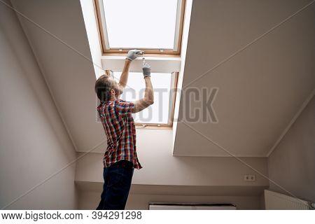 Young Caucasian Repairman Screwing Handle On Skylight Window