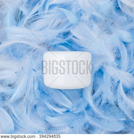 Spa Cosmetic Product, White Cream Jar, Branding Mock Up, Top View On Blue Feathers Background. Flat