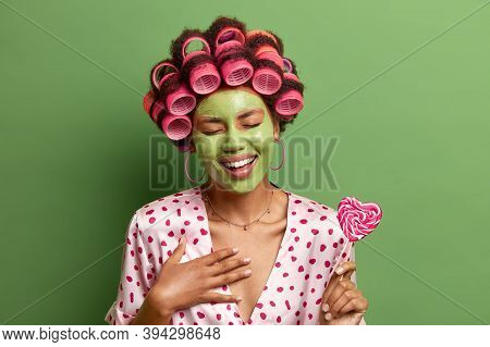 Indoor Shot Of Overjoyed Lady Giggles Positively Over Something Very Funny, Closes Eyes From Laughte