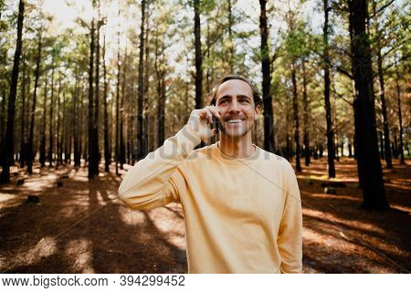 Young Caucasian Teen Chatting On Smartphone Standing In Luscious Woodlands