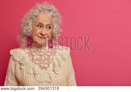 People, Aging And Cosmetology Concept. Wrinkled Grey Haird Senior Woman Gazes Delighted Aside, Wears