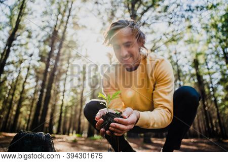 Caucasian Male Holding Little Plant In Soil Crouching In Luscious Woodlands Caring For Nature And Th