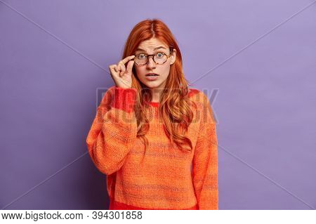 Pretty Shocked Redhead Woman Stares Impressed And Keeps Hand On Rim Of Spectacles Wears Warm Sweater