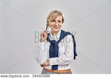 Portrait Of Elegant Middle Aged Caucasian Woman Wearing Business Attire Holding Her Glasses, Smiling