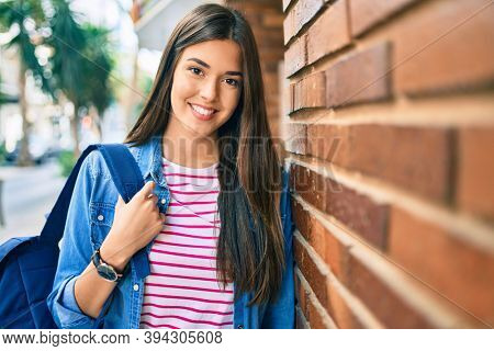 Young hispanic student girl smiling happy leaning on the wall at the city.