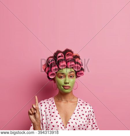 Confident Ethnic Woman With Hair Rollers, Green Facial Mask, Looks Mysteriously At Camera, Points Ab