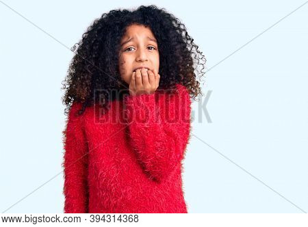 African american child with curly hair wearing casual winter sweater looking stressed and nervous with hands on mouth biting nails. anxiety problem.