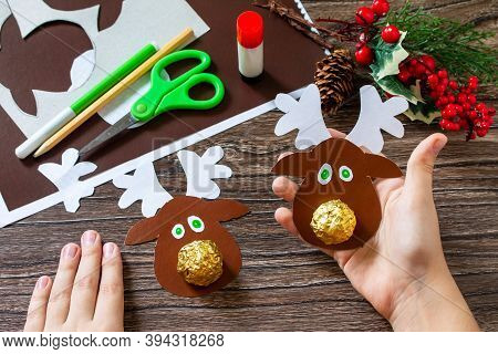 Child Holding A Gift With Candy Christmas Deer. Handmade. Children's Creativity Project, Crafts, Cra