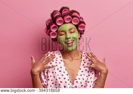 Portrait Of Pleased Young African American Woman Stands With Closed Eyes, Smiles Gently, Imagines So