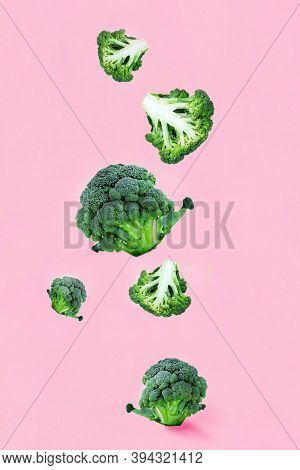 Falling Soaring Green Broccoli Slices On A Pink Background. Concept Of Flying Food, Green Vegetables