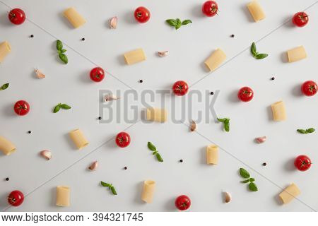 Raw Rigatoni Pasta Made Of Durum Wheat Flour, Red Ripe Tomatoes And Green Basil On White Background.