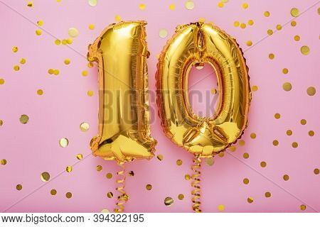 10 Air Balloon Numbers On Pink Background. 10 K Gold Foil Balloons With Confetti. Birthday Party Fla