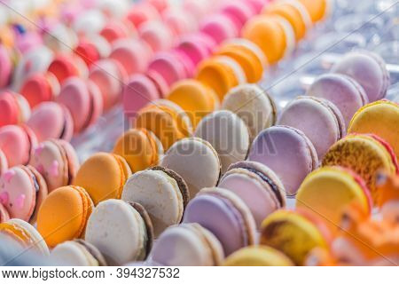 Assortment Of Colorful Macarons Cakes For Sale On Counter Of Candy Shop, Market, Cafe Or Bakery. Row