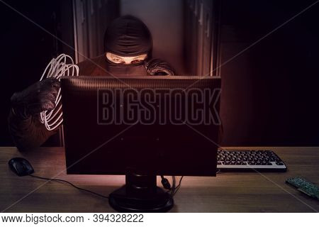 A Hacker In A Black Mask With Wires In His Hand In A Server Room. Concept Of Data Security Problems