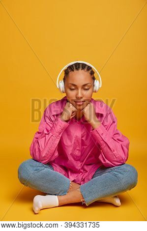 People And Lifestyle Concept. Relaxed Dark Skinned Girl Sits With Closed Eyes, Keeps Hands Under Chi