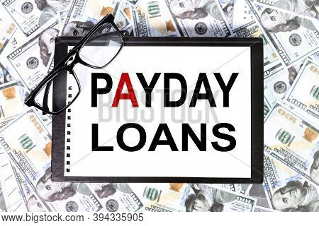 Payday Loans, Text On White Paper On The Background Of Money, Banknotes, Dollars