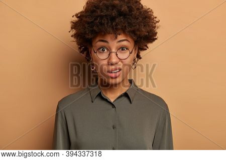 Discontent Young African American Woman Expresses Scorn And Disbelief, Smirks Face With Dissatisfact