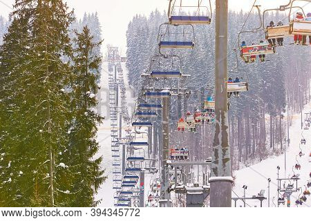 Bukovel, Ukraine - January 09, 2019 - Cable Car With Skiers And Tourists In Winter. Forest Recreatio