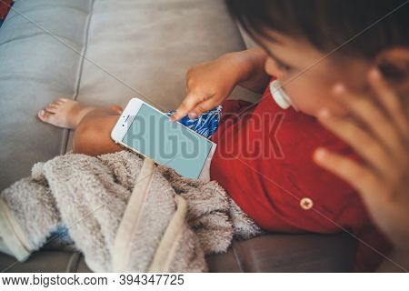 Caucasian Small Boy Is Sitting In Bed And Holding A Phone While Looking At The Screen Covered With A