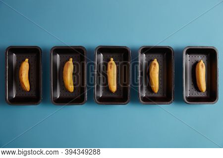 Above Shot Of Unpeeled Yellow Bananas Packed On Trays For Selling Isolated On Blue Studio Background