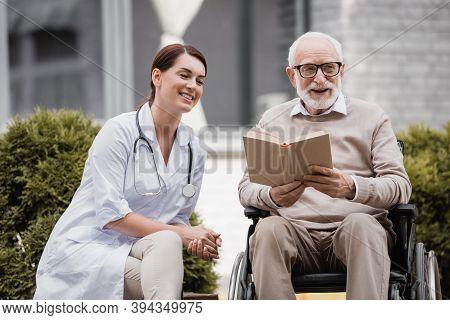 Geriatric Nurse Near Aged Disabled Man Reading Book In Wheelchair Outdoors